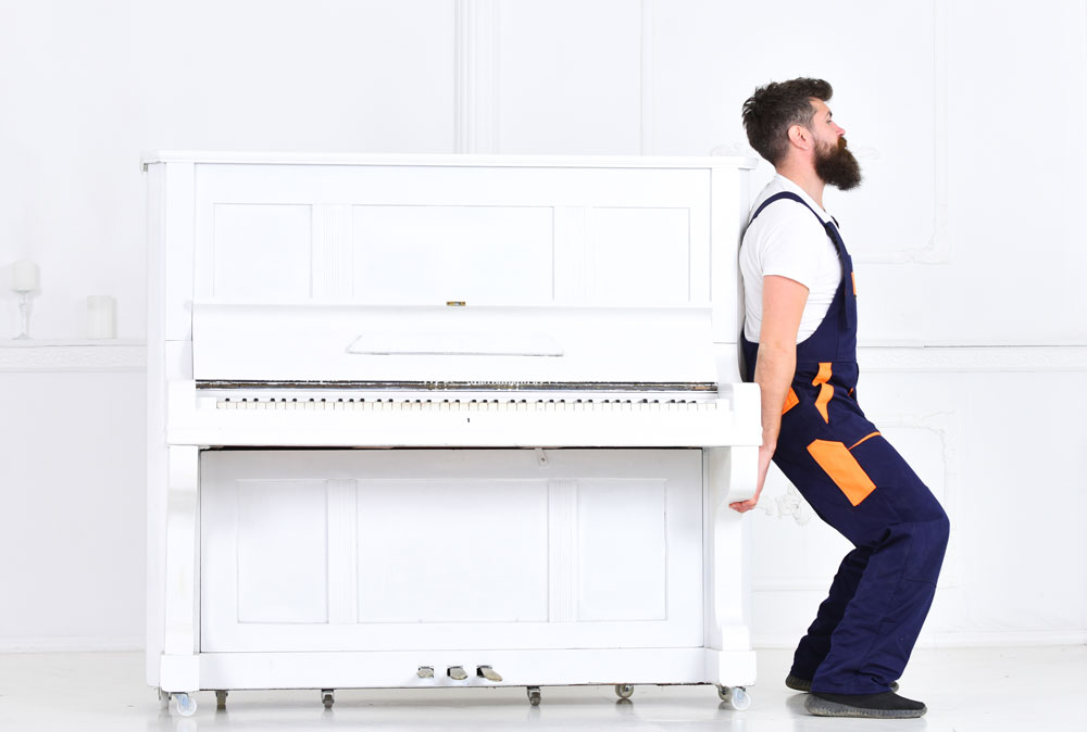 Bearded man attempting to lift a heavy piano